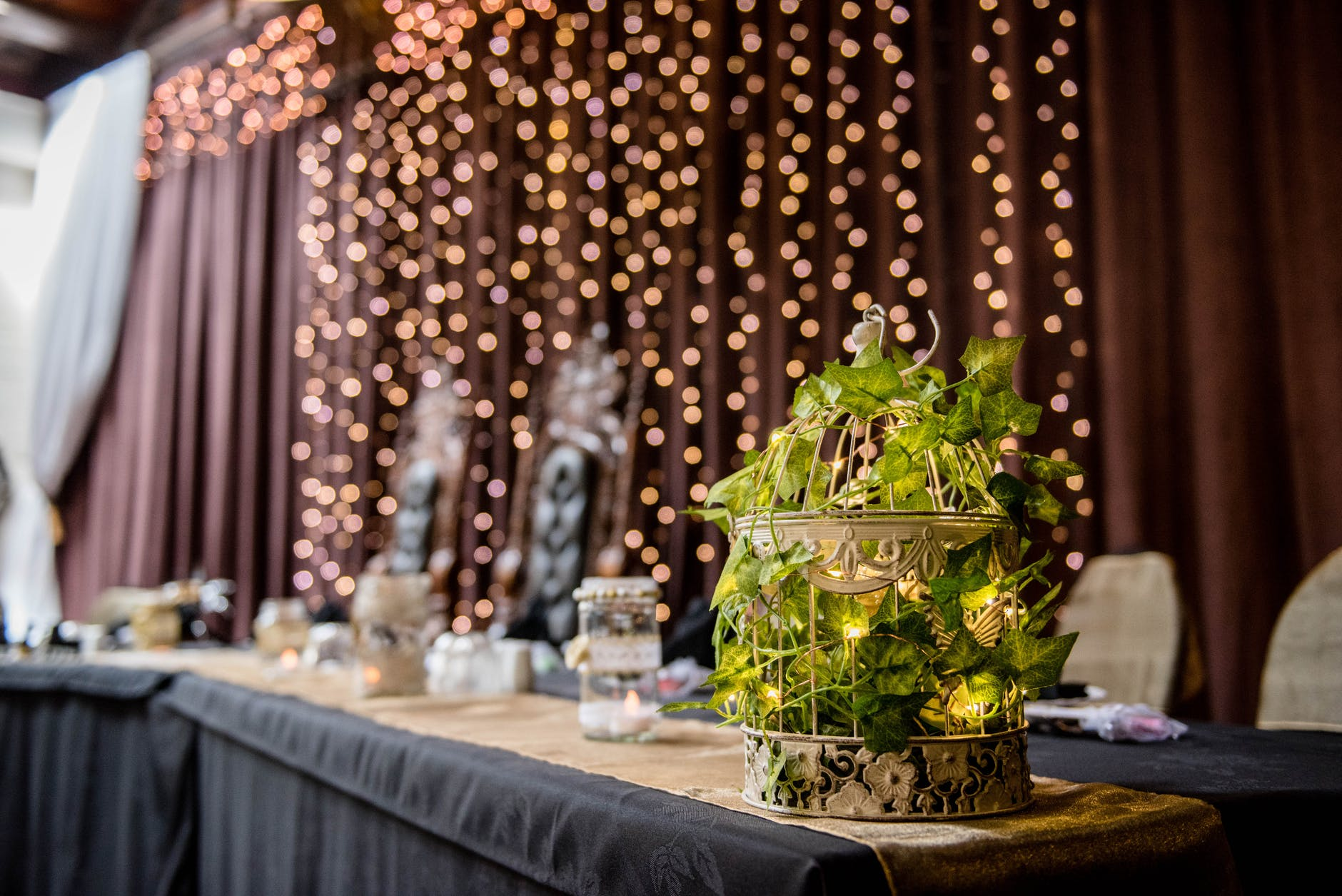 banquet table with candles against wall with garland decorations