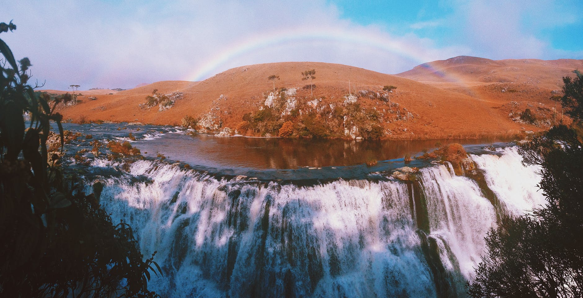 majestic waterfall and hill under rainbow