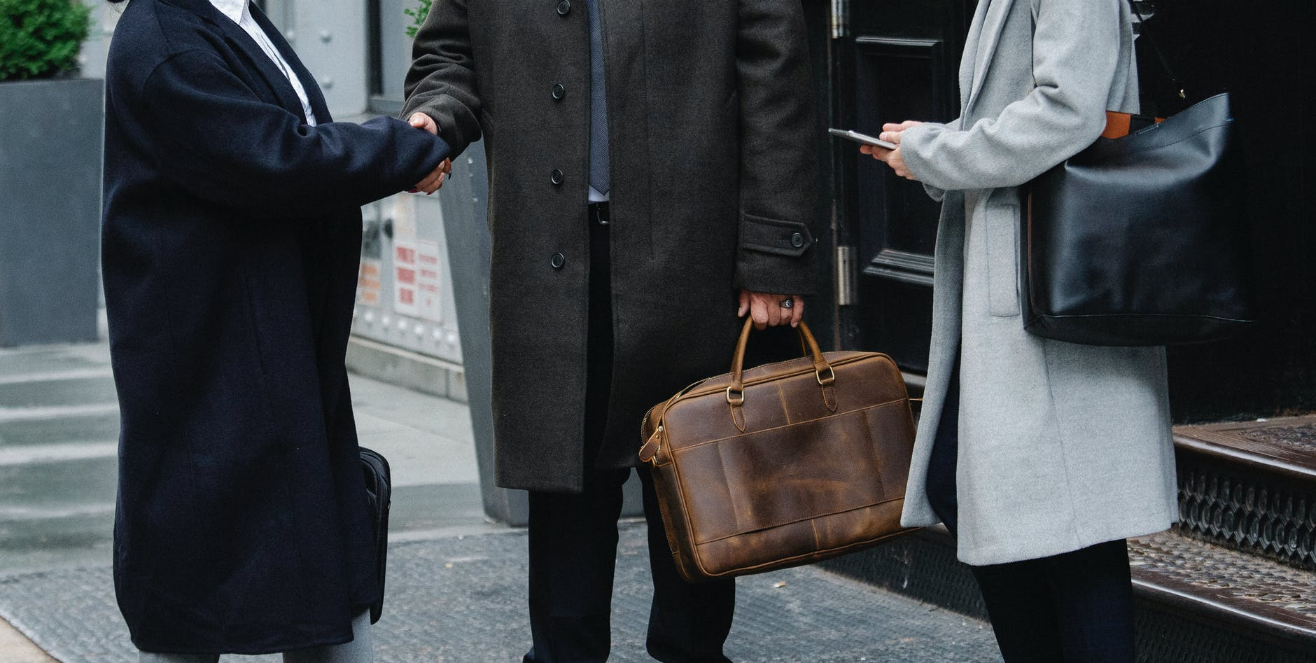 stylish businesspeople in outerwear shaking hands