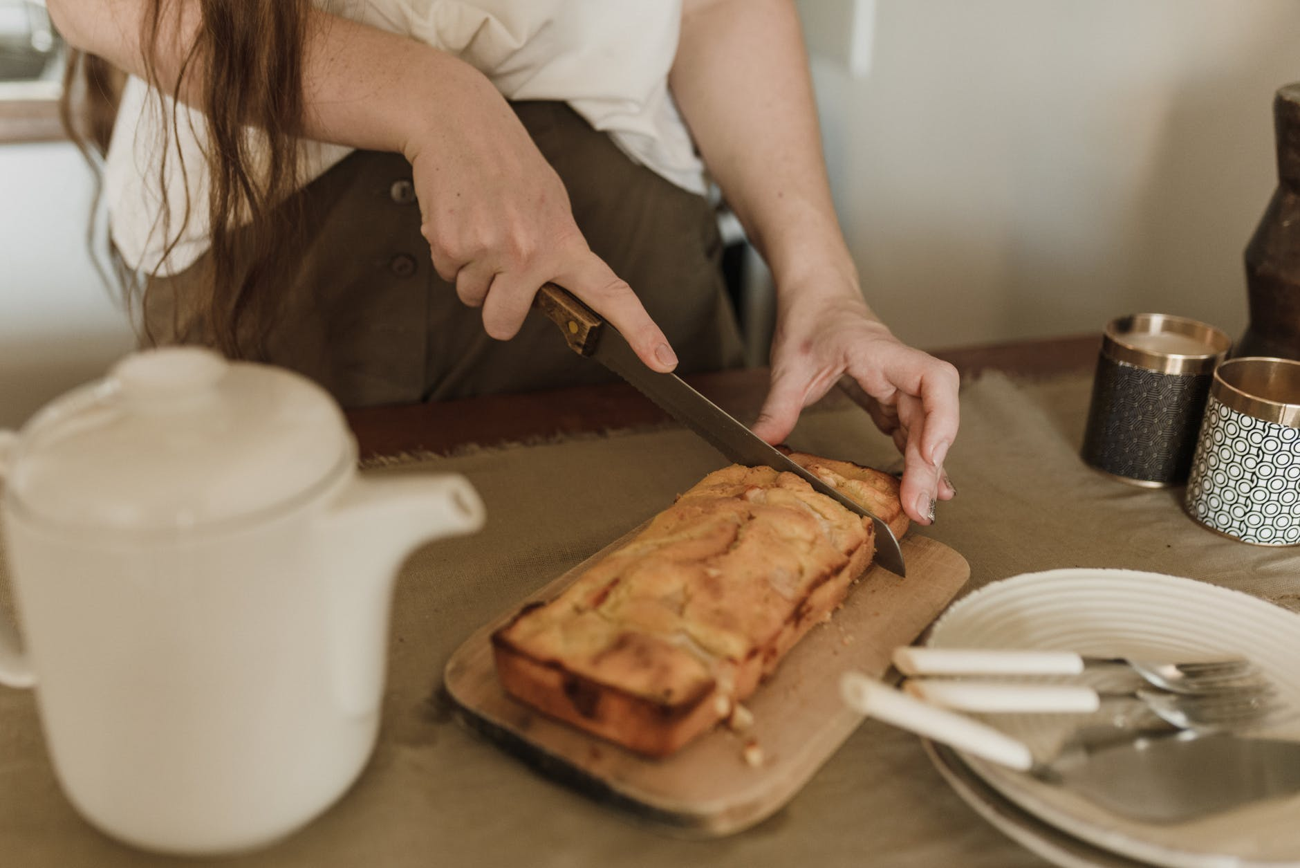 unrecognizable woman cutting freshly baked sweet bread in kitchen
