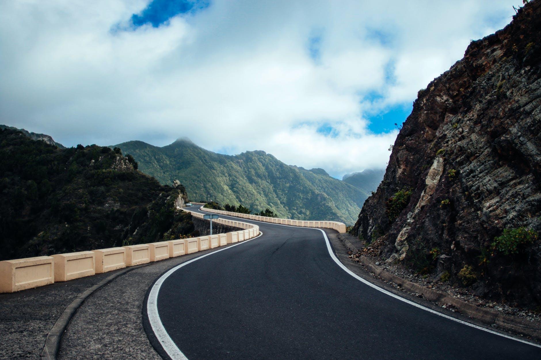 black asphalt road near cliff mountain