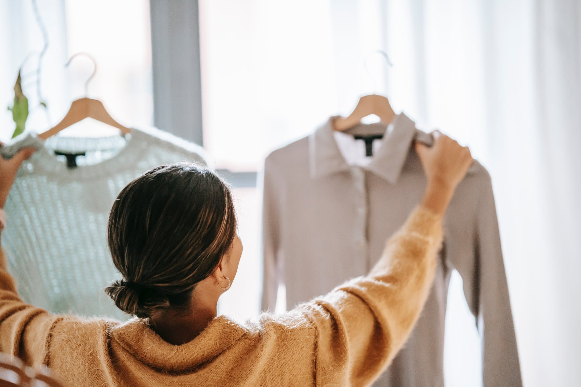 anonymous woman choosing clothes in store