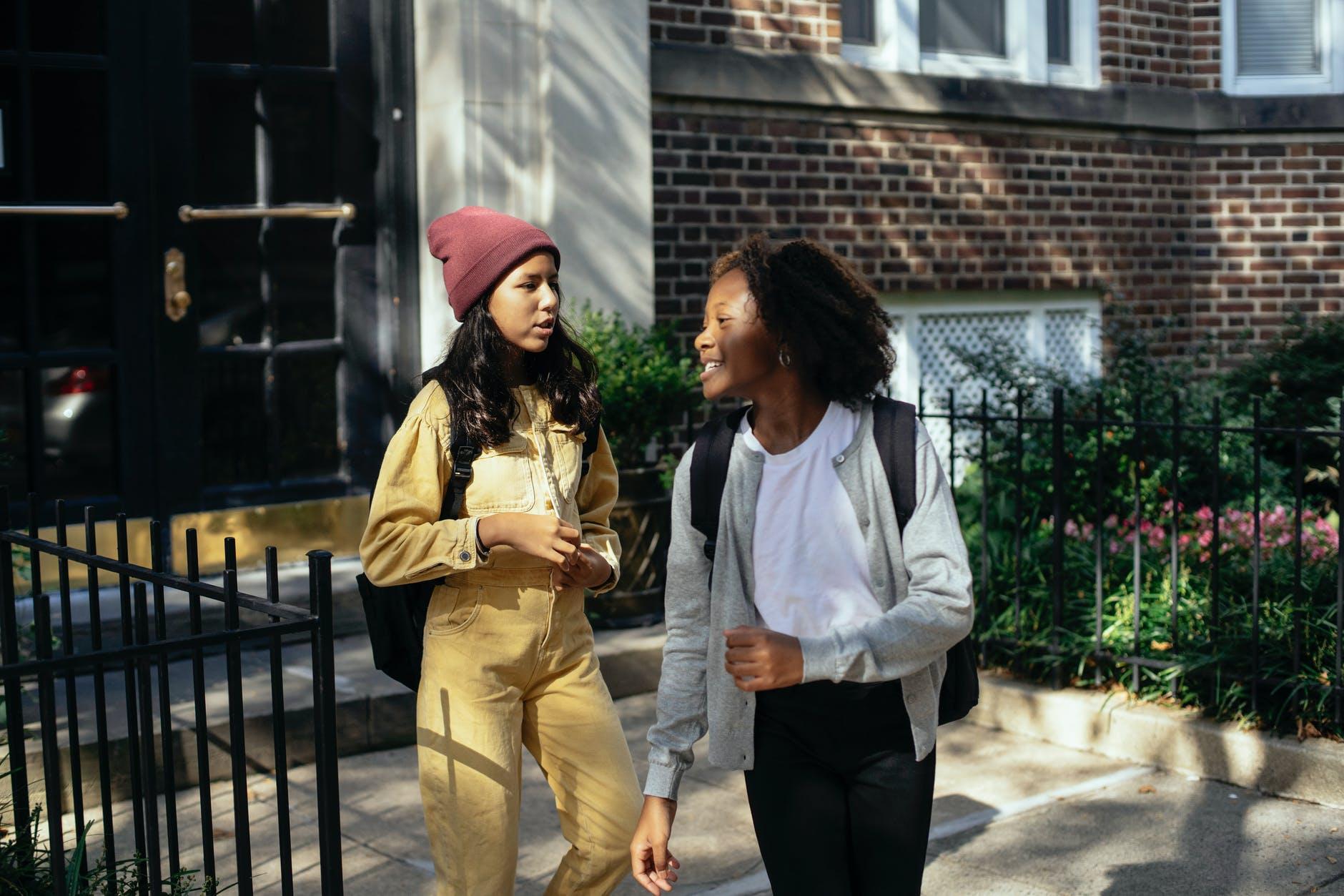 cheerful diverse girls talking on street