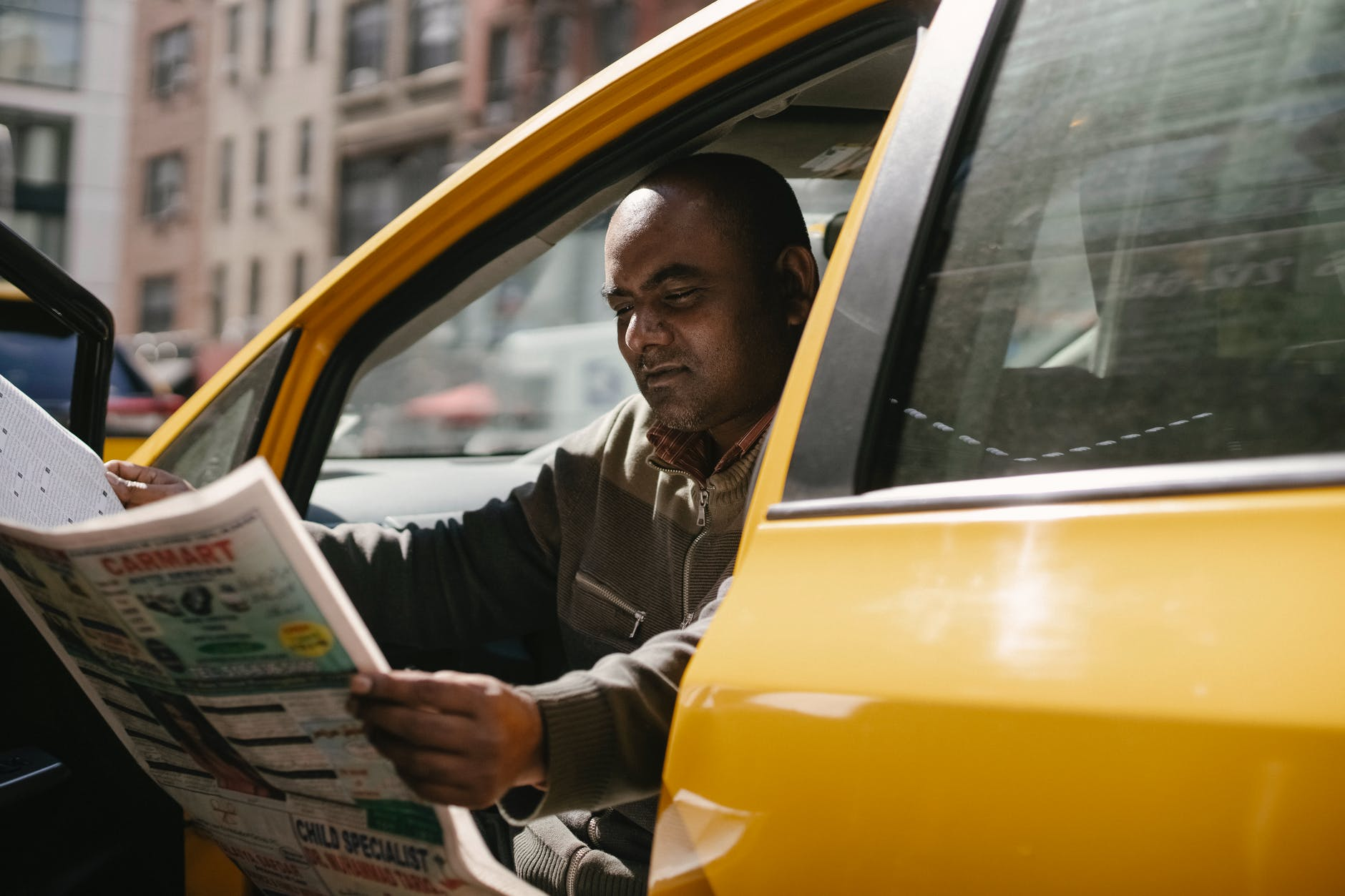 ethnic man sitting in cab with newspaper
