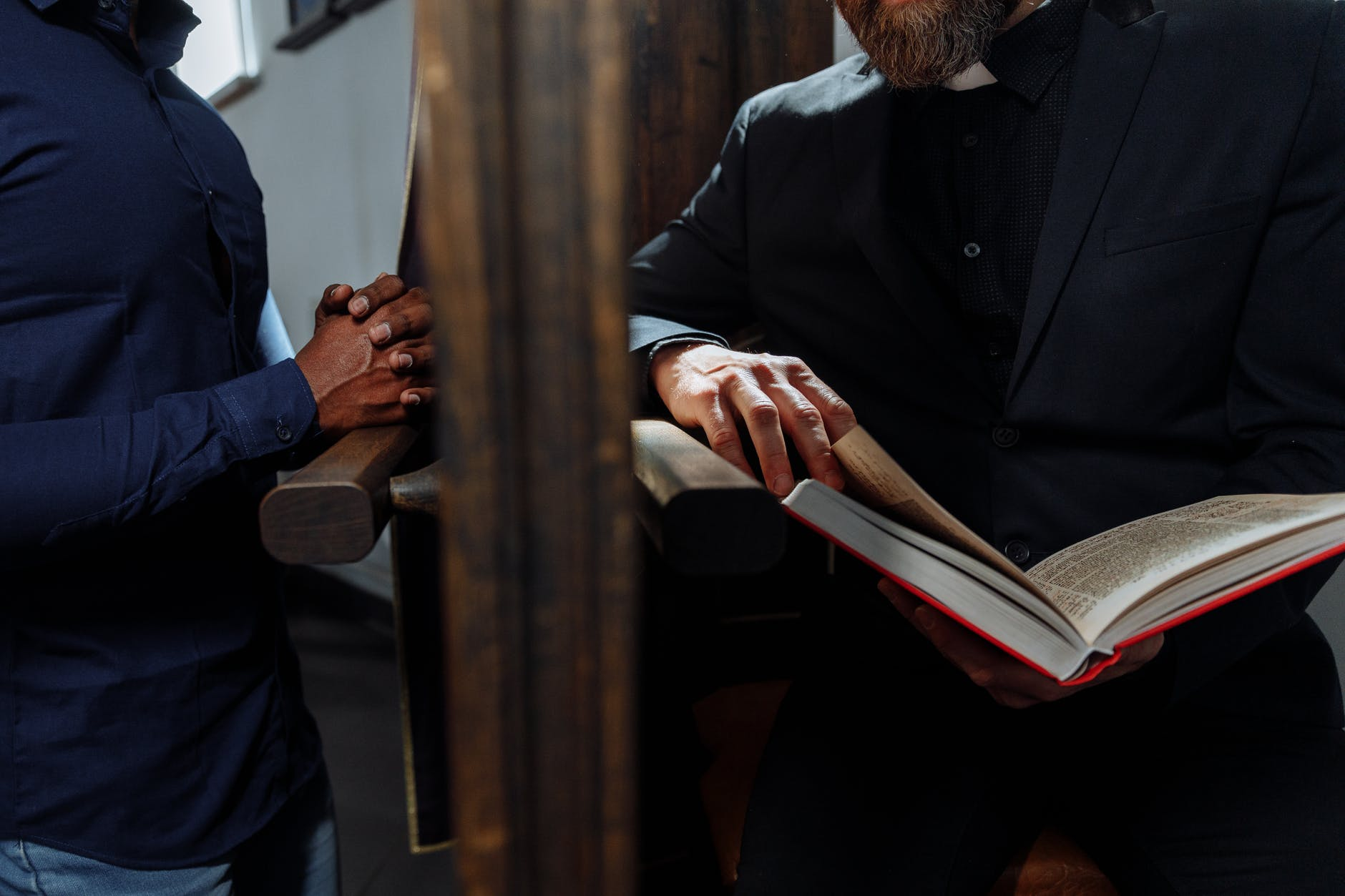 priest holding bible behind wooden wall while man confessing